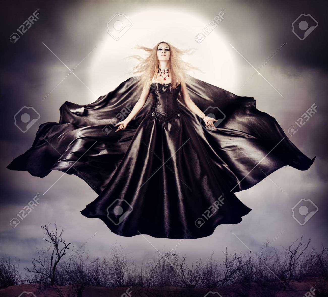 Beautiful woman  flying halloween witch in midnight outdoor about full moon with black developing cloak Stock Photo - 40818303
