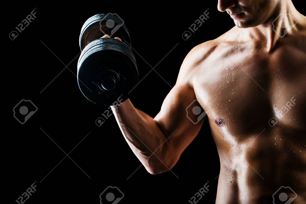 Focus on stomach. Dark contrast shot of young muscular fitness man stomach and arm. Stock Photo - 45059561