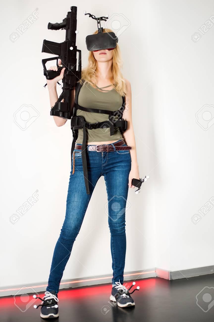 Beautiful sexy blond girl model gamer wearing headset of virtual