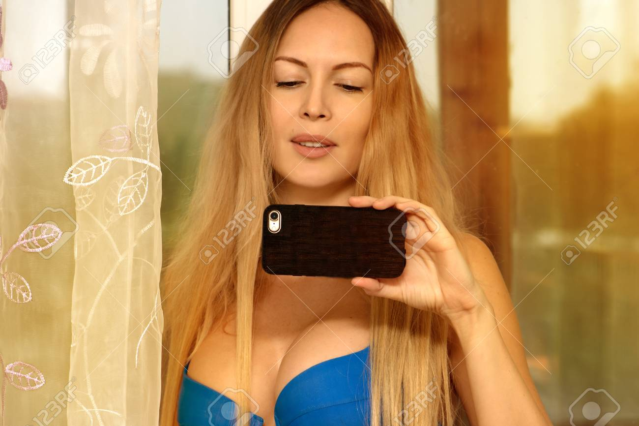A Beautiful Girl With Long Light Brown Hair Holds A Mobile Phone