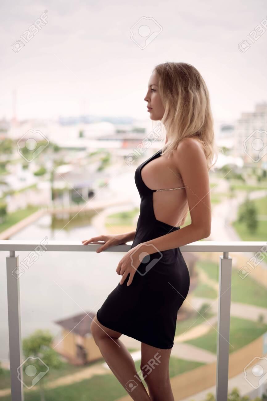 Young beautiful blond fashion woman model wearing black dress with open back - 125205070