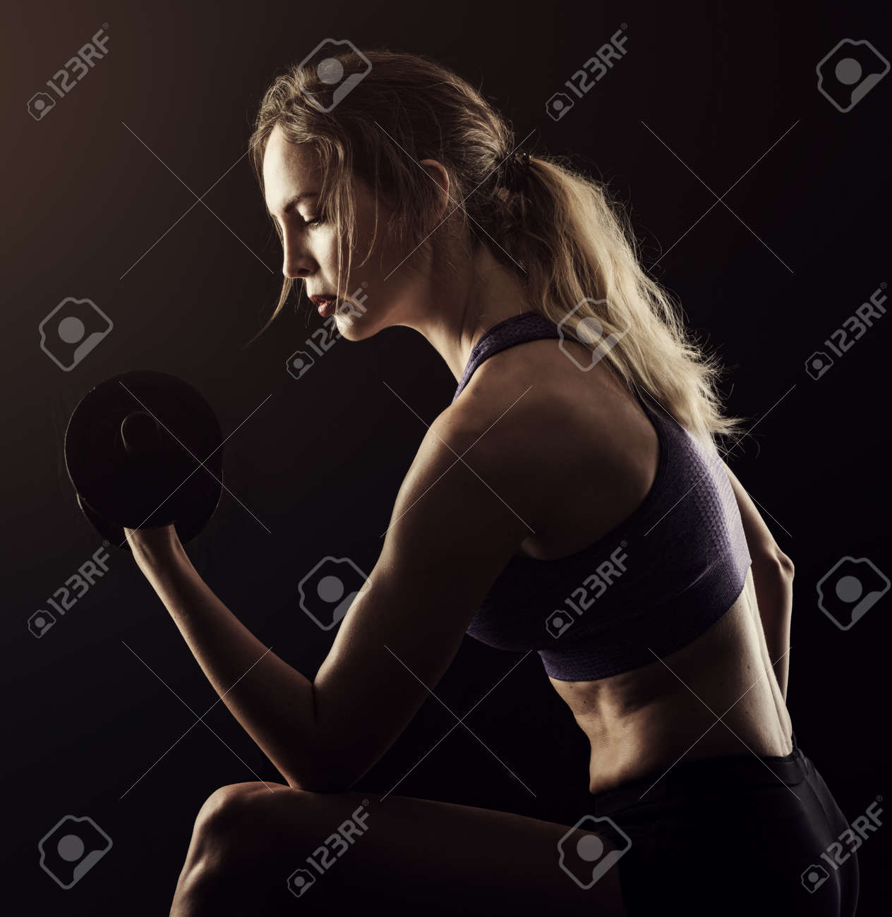 Slim athletic woman Holding dumbbell in the hand on black - 168249066