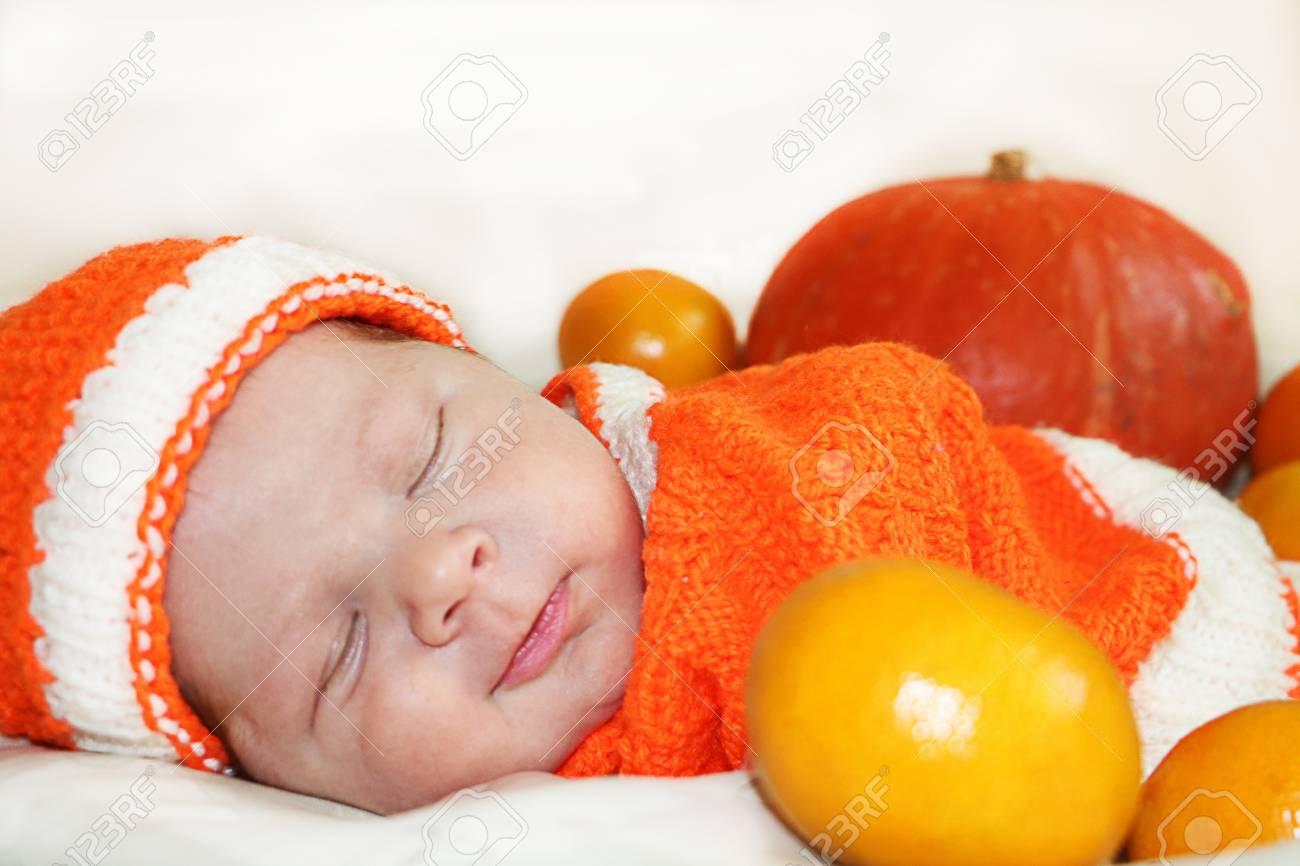 Cute sleeping newborn baby dressed in a knitted orange costume with a pumpkin and oranges background & Cute Sleeping Newborn Baby Dressed In A Knitted Orange Costume ...