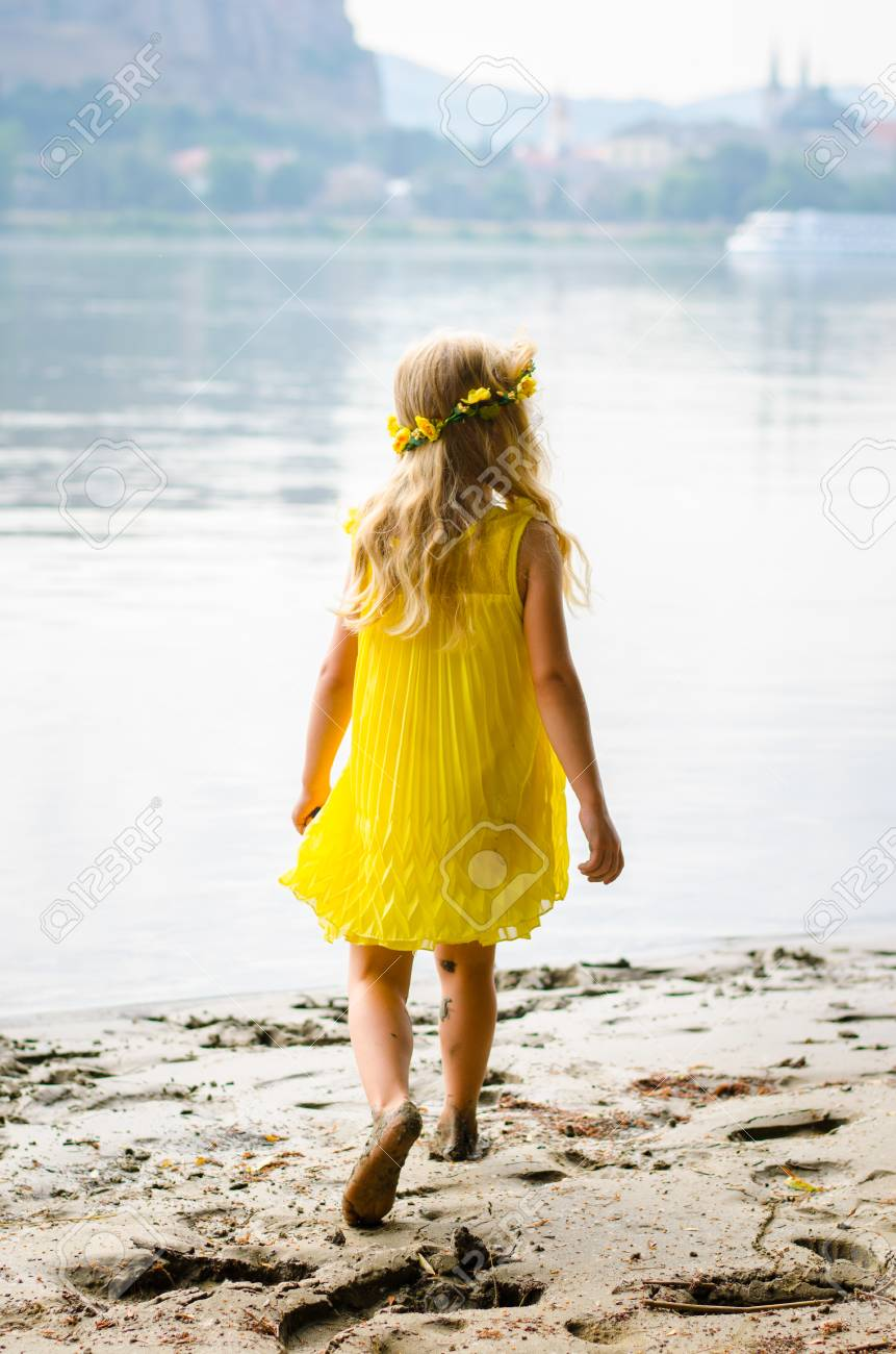 Beautiful Blond Girl In Yellow Dress With Flower Headband By Stock