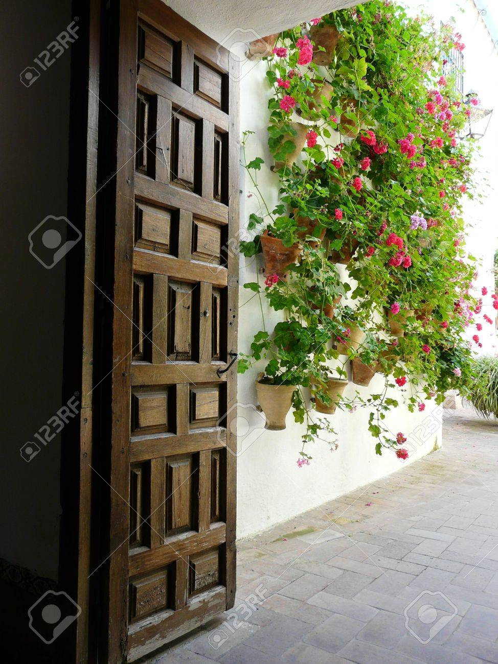 Old wooden doorway and courtyard with geraniums at the Palacio de Viana in Cordoba, Spain Stock Photo - 7302286