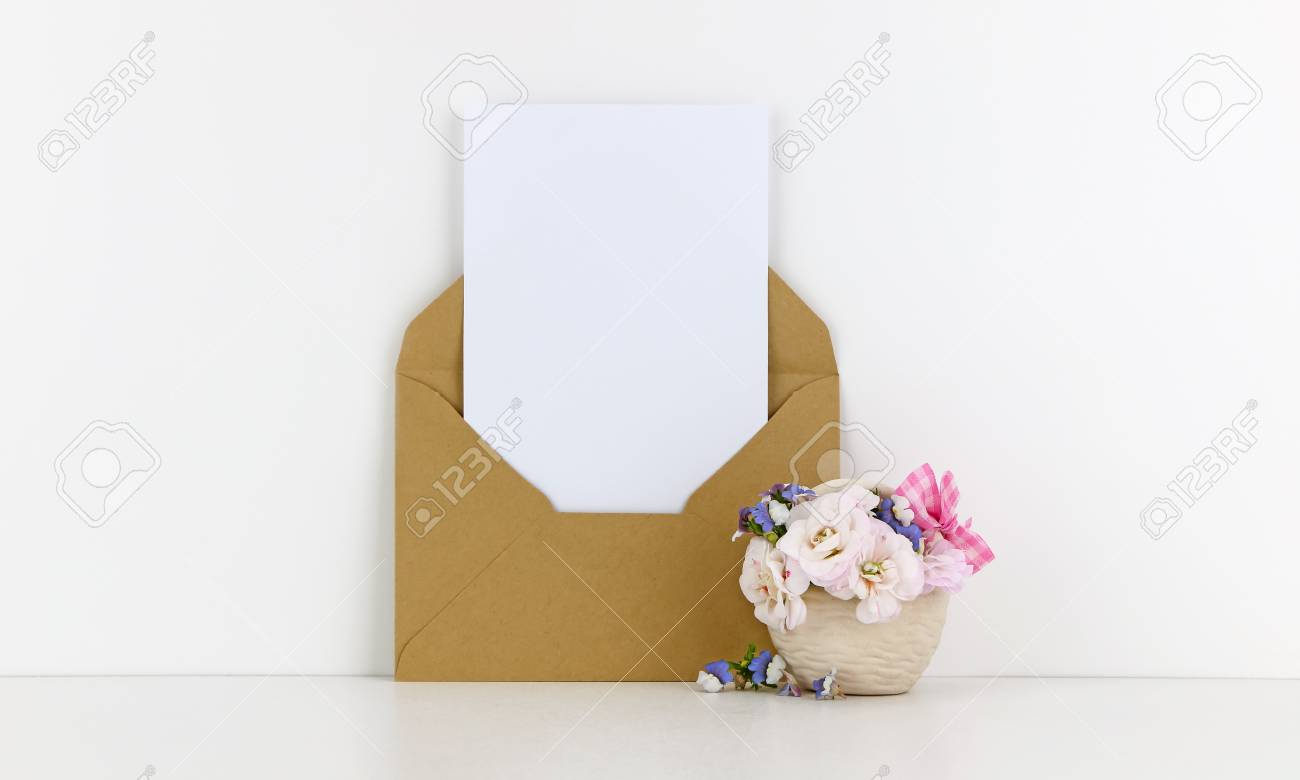 blank postcard mockup with craft paper envelope and white flowers