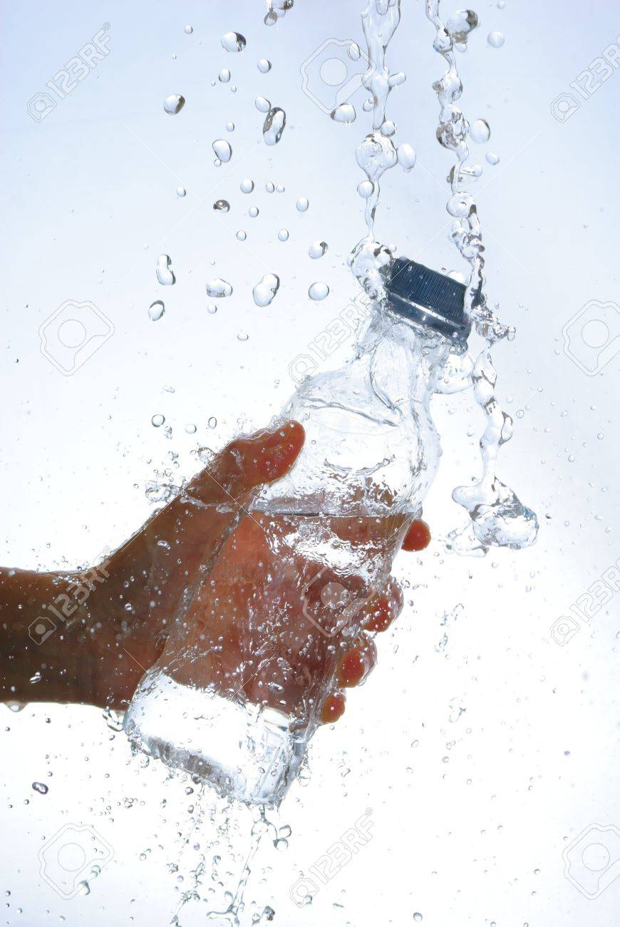 Water bottle in hand, in a spray of water droplets Stock Photo - 13405822