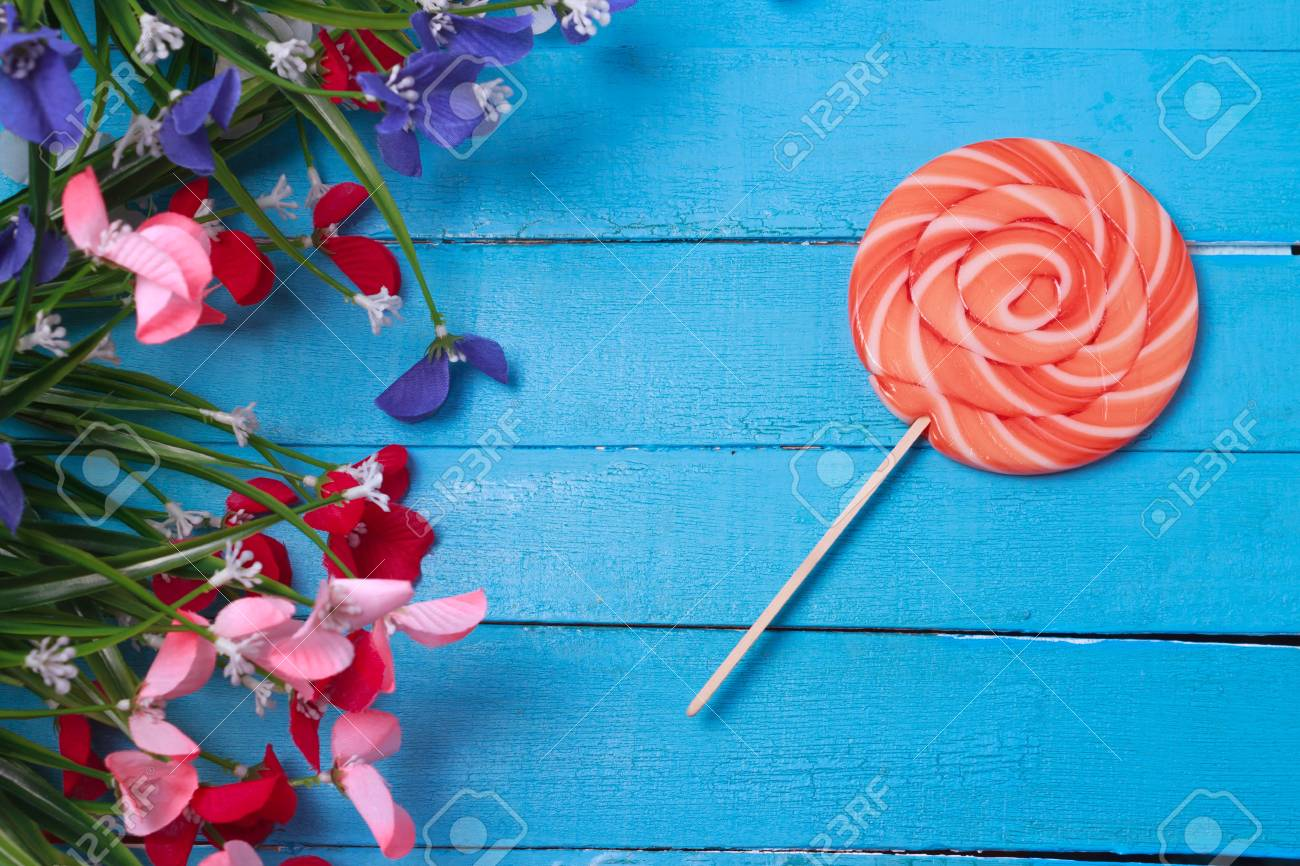 Bright Birthday Background With Sweets And Decorations Lollipop On Turqiouse Flowers Stock Photo