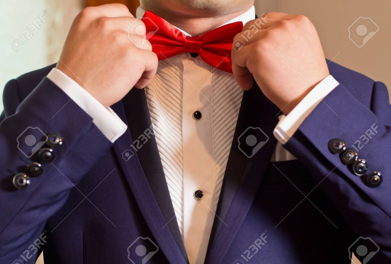 f9516a81 Groom in a white shirt and blue suit correcting red bow tie Stock Photo -  40397497