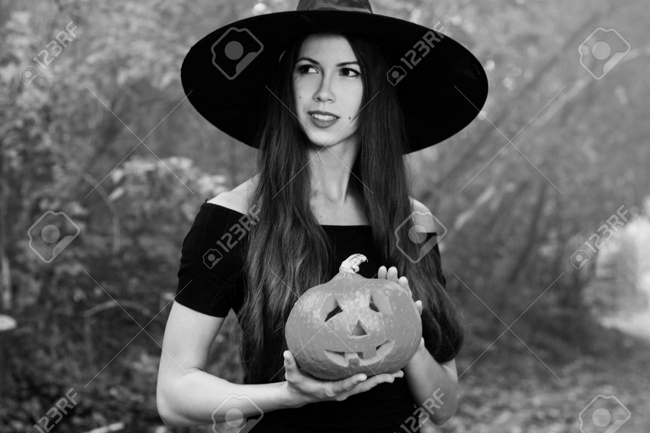 55999eeee40 Halloween Witch with a halloween pumpkin jack o lantern decor with funny  face in a dark forest. Beautiful young woman in witches hat and costume  holding ...