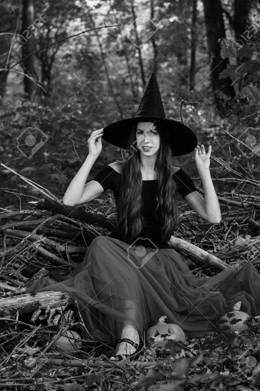 49caba56512 Halloween Witch with a halloween pumpkin jack o lantern decor with funny  face in a dark forest. Beautiful young woman in witches hat and costume.