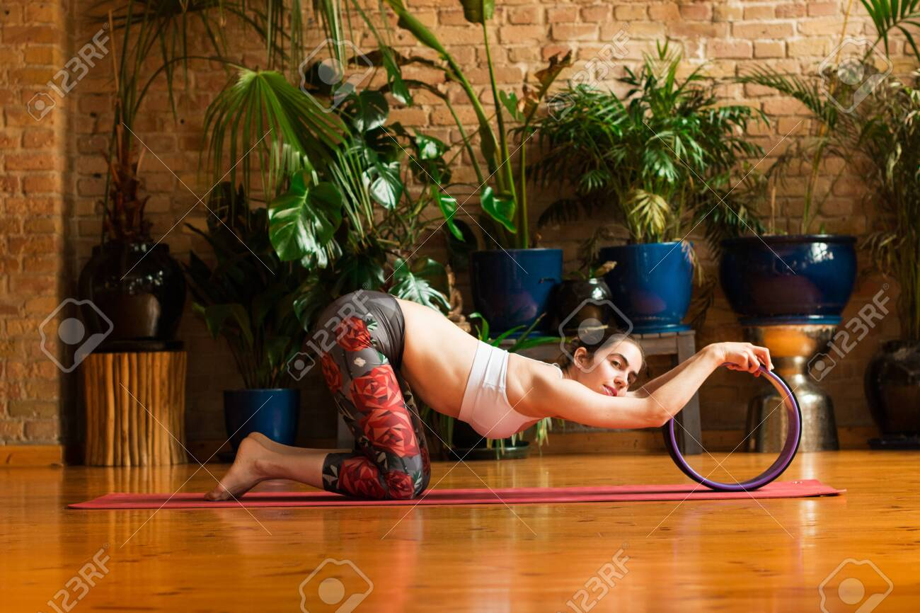 Young woman practicing yoga in studio. Sitting on red yoga mat and stretching with yoga ring. Loft and stylish interior (wooden floor and brick wall). Healthy and sport concept. - 147483451