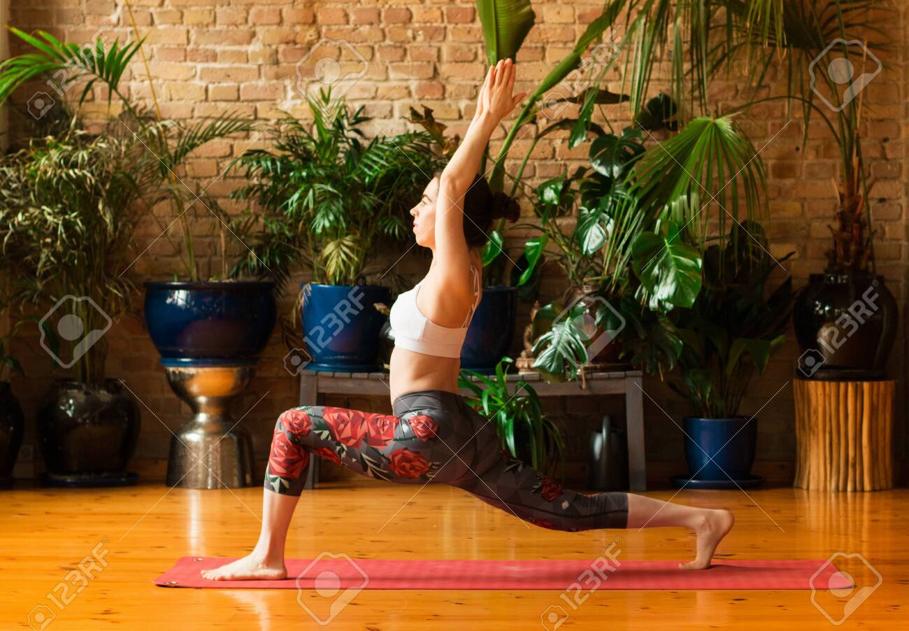 Young woman practicing yoga in studio. Staying on red mat and meditating, holding hands together, making split. Loft interior with wooden floor and brick walls. Healthy and sport concept. - 145366148