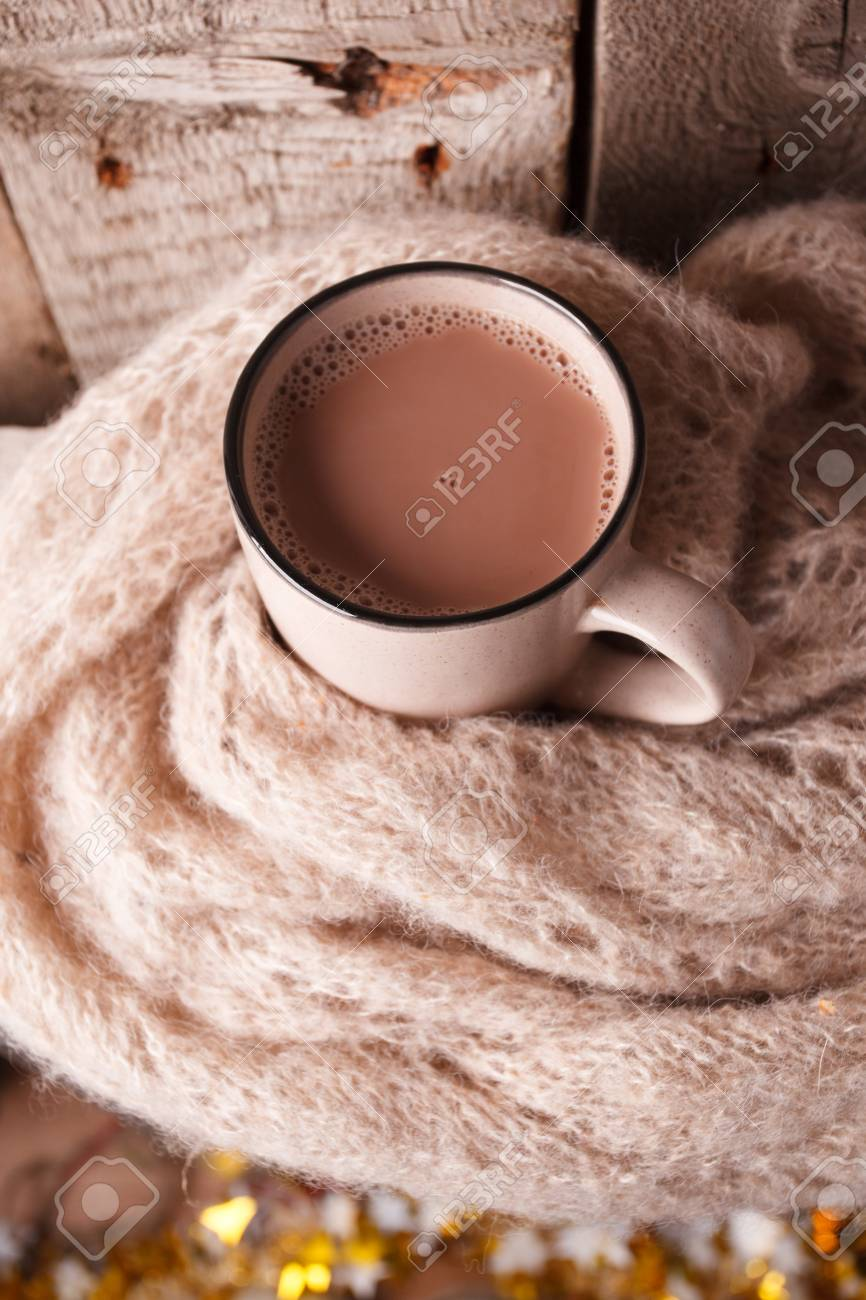 Details of still life in the home interior living room. Beautiful Cup of hot cocoa or chocolate and sweaters on wooden background . Cosy autumn-winter concept - 109743538