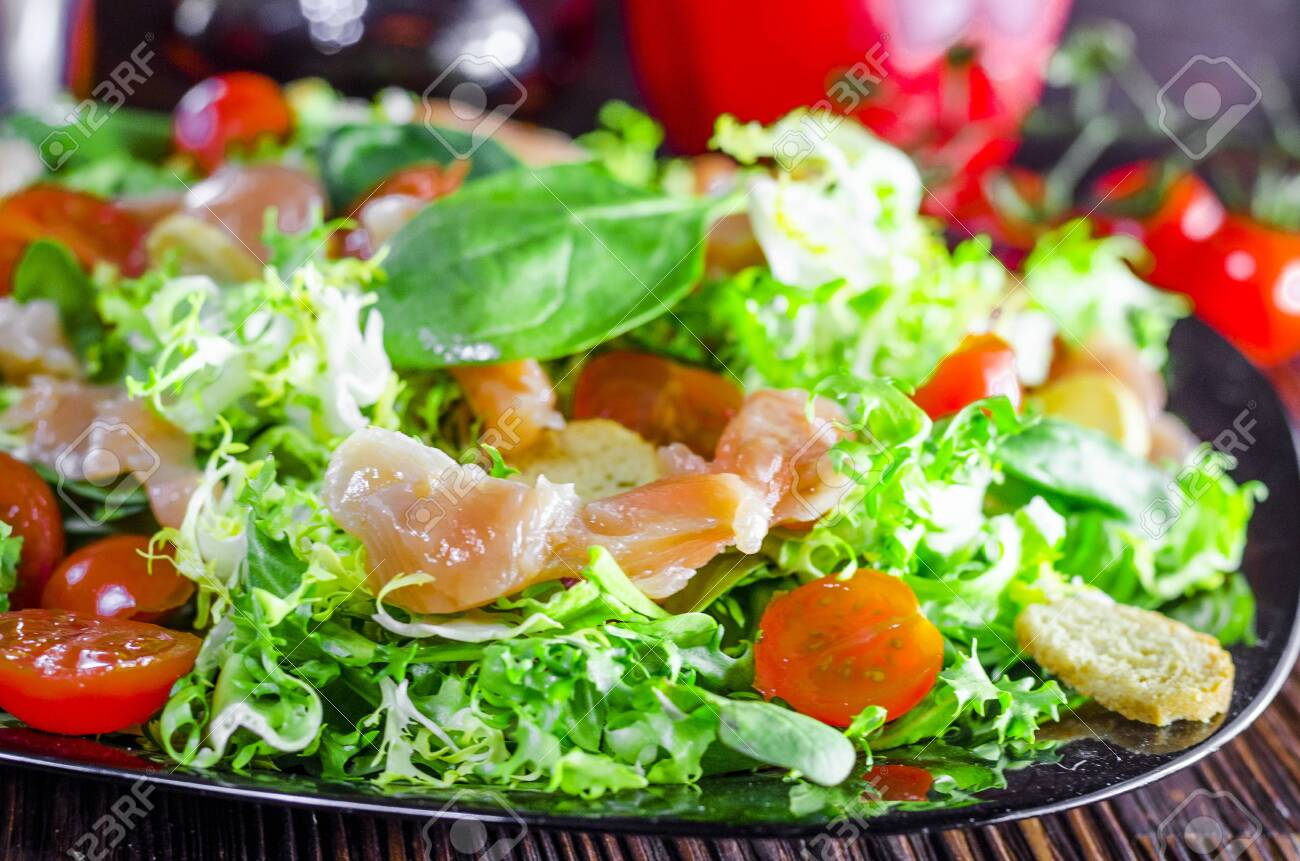 dietary salad with red fish in a plate close-up - 124323047
