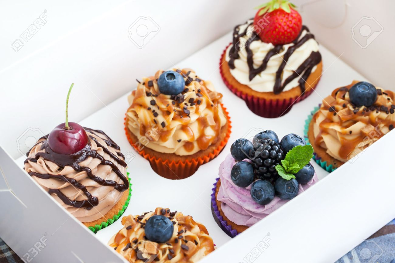 Set Of Different Delicious Cupcakes In A Paper Box Stock Photo