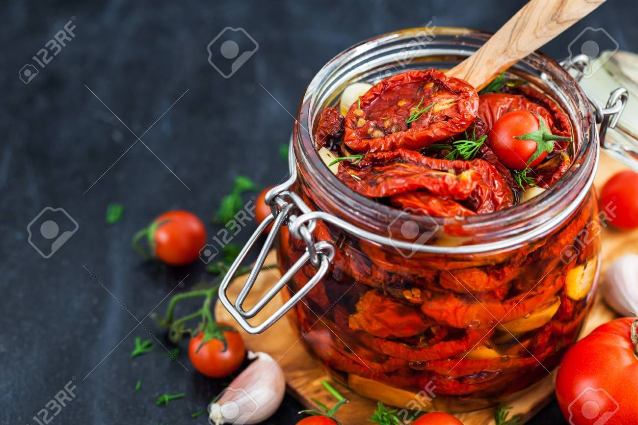 Sun dried tomatoes with garlic and olive oil in a jar on dark background - 87157958