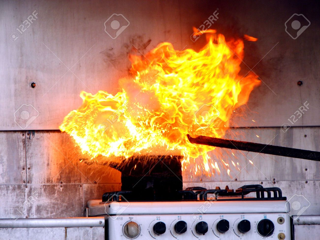 Putting water on oil fire on stove Stock Photo - 12932938