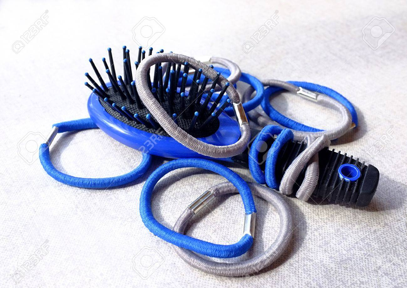 A few simple blue and gray elastic hair bands and a small hair-brush Stock ffc67ed0627