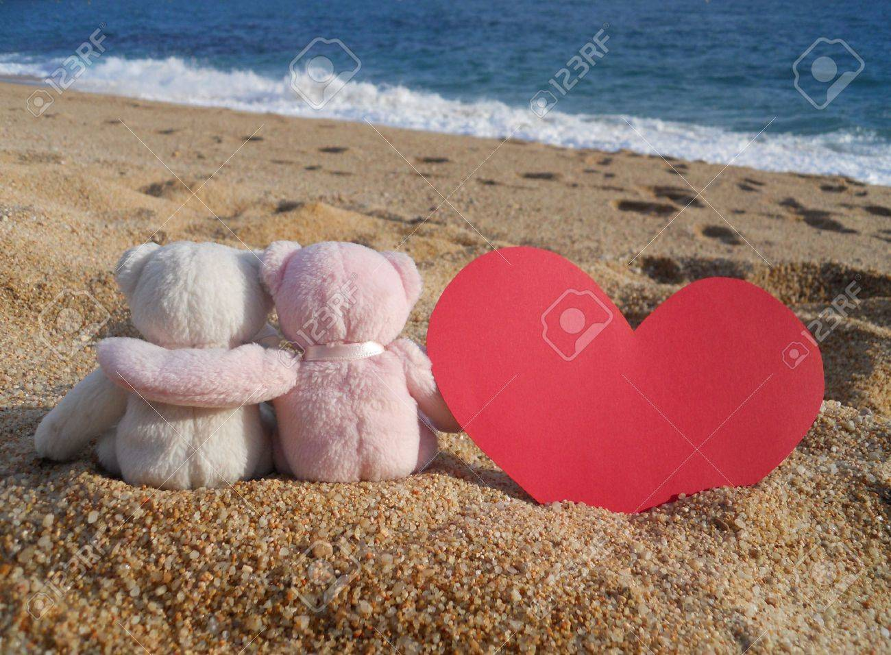 teddy bears romance (white and pink stuffed animal teddy bears toys with red heart sitting on the beach) Stock Photo - 8879409