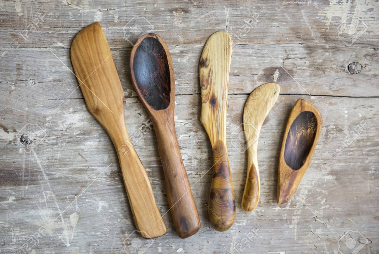 old handmade wooden spoons on old rustic kitchen table