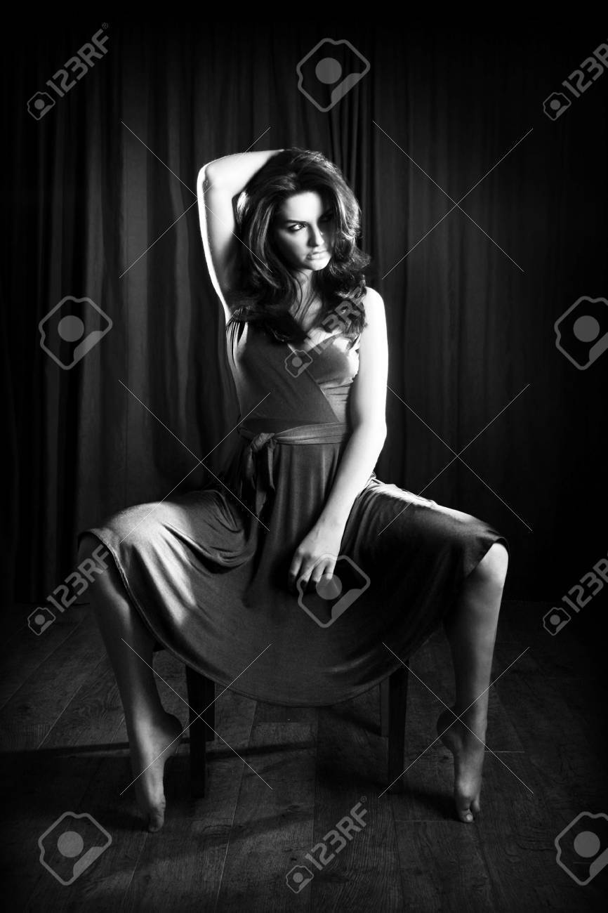 A glamorous young woman sitting on a stool and looking to the side. Stock Photo - 7033125