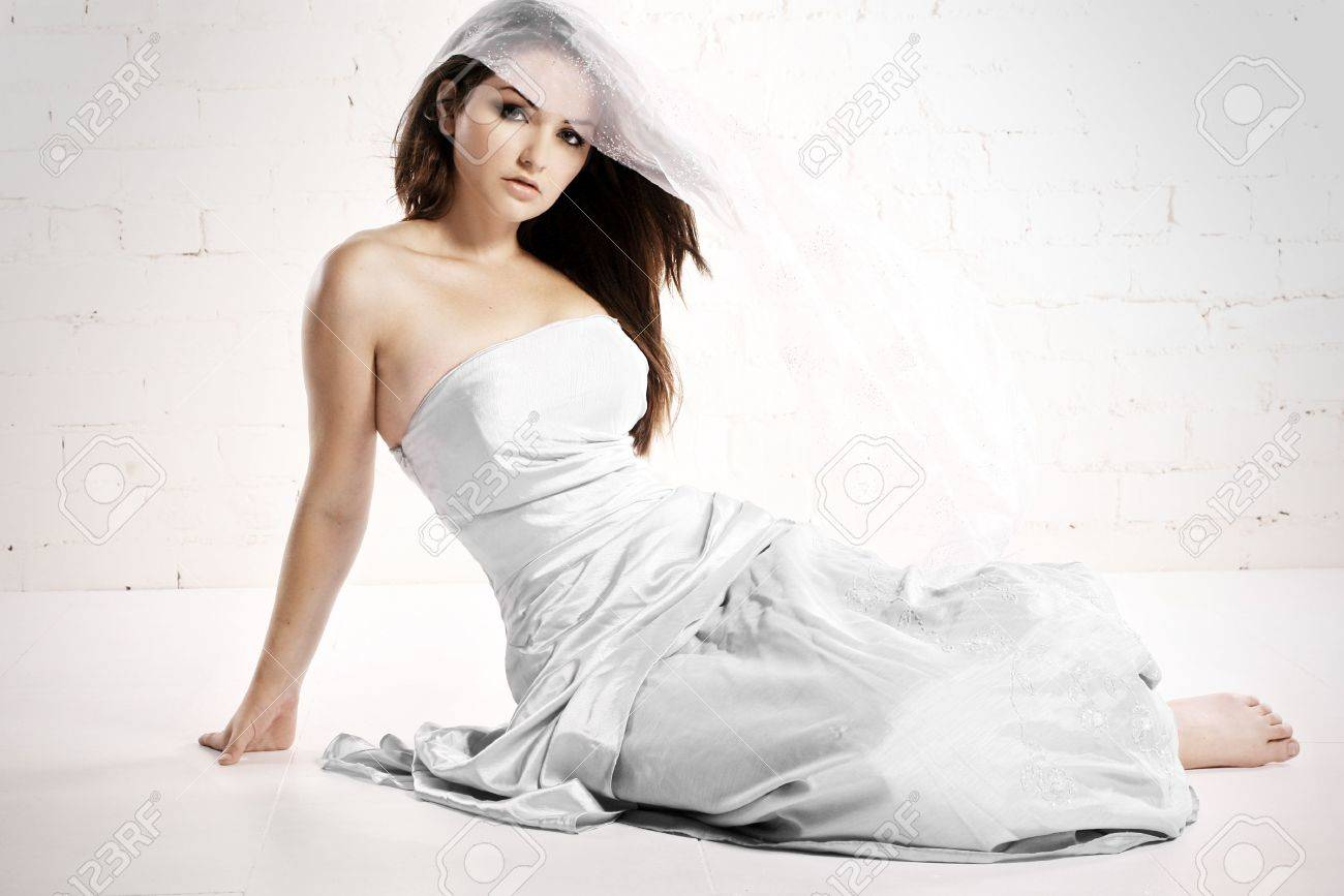 A pretty young woman in bridalwear in a white studio with wind in her hair. Stock Photo - 7421125