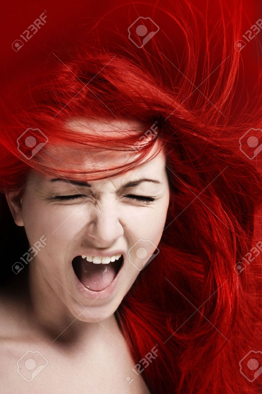 A furious young woman with her hair red like fire. Stock Photo - 7630145