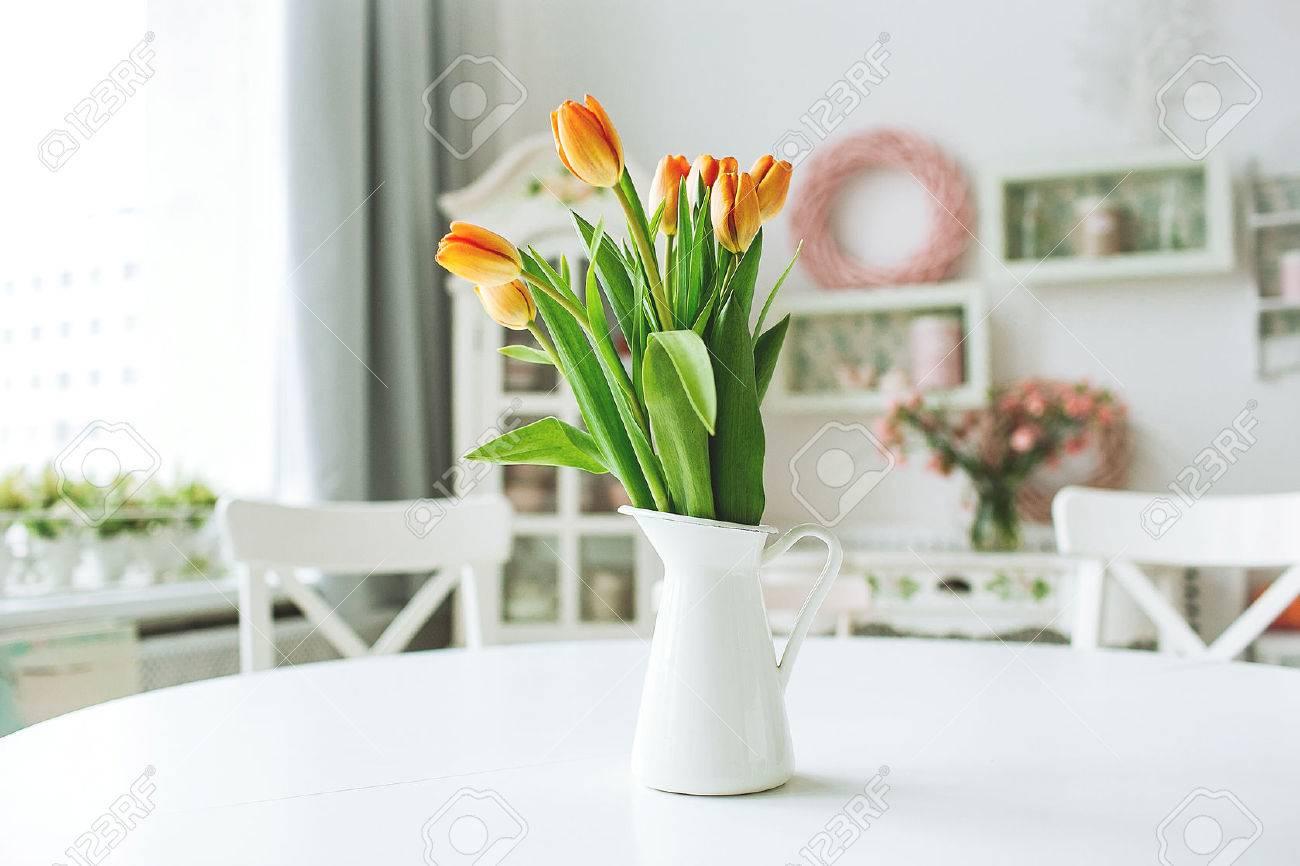 Flores anaranjadas hermosas en un florero en un blanco mesa de la cocina  rústica