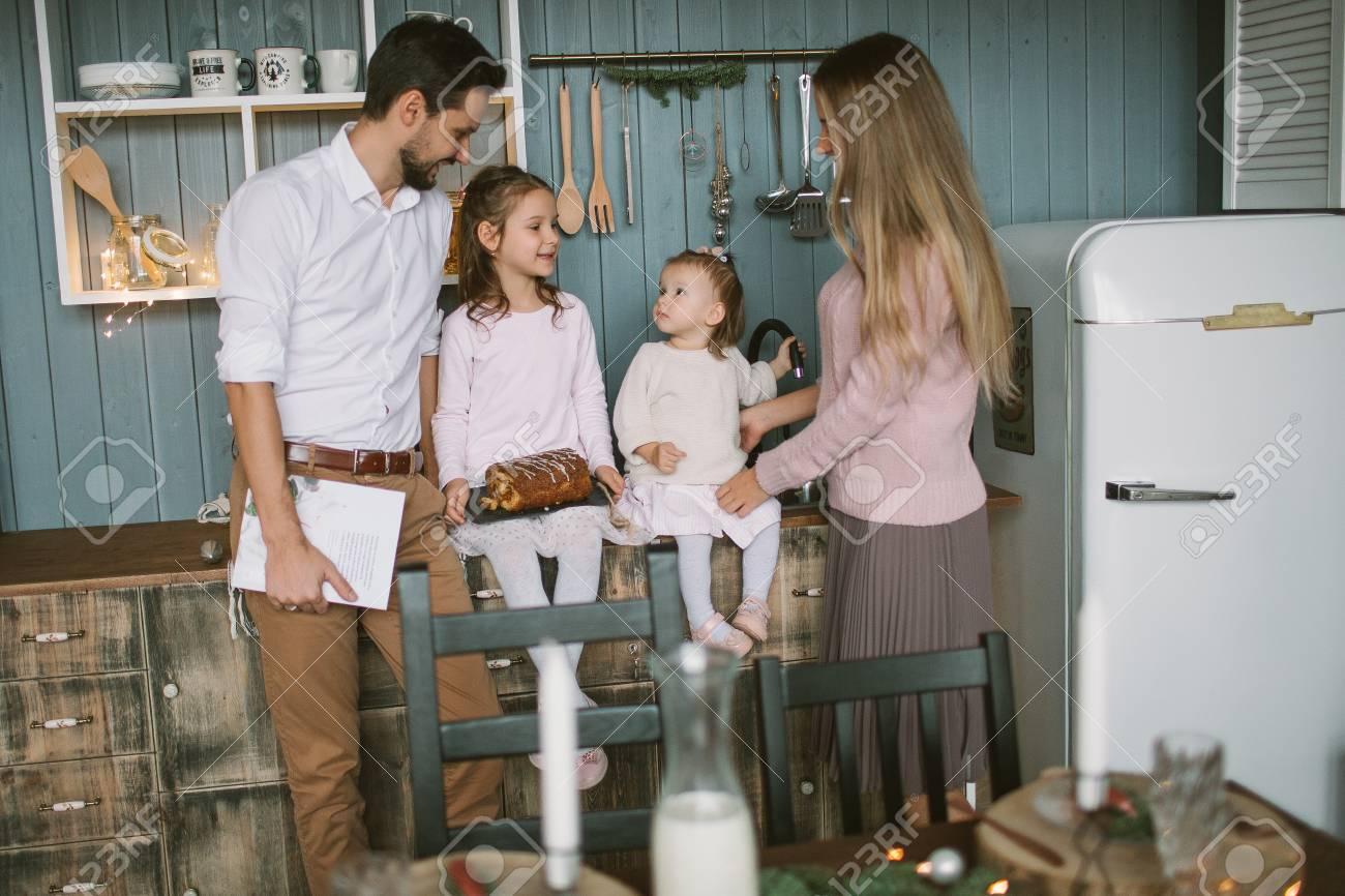 Jonge ouders en kleine dochters met taart vieren kerstmis op