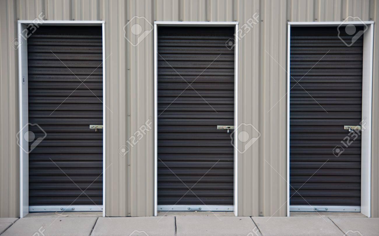three brown metal doors of an outdoor storage unit stock photo