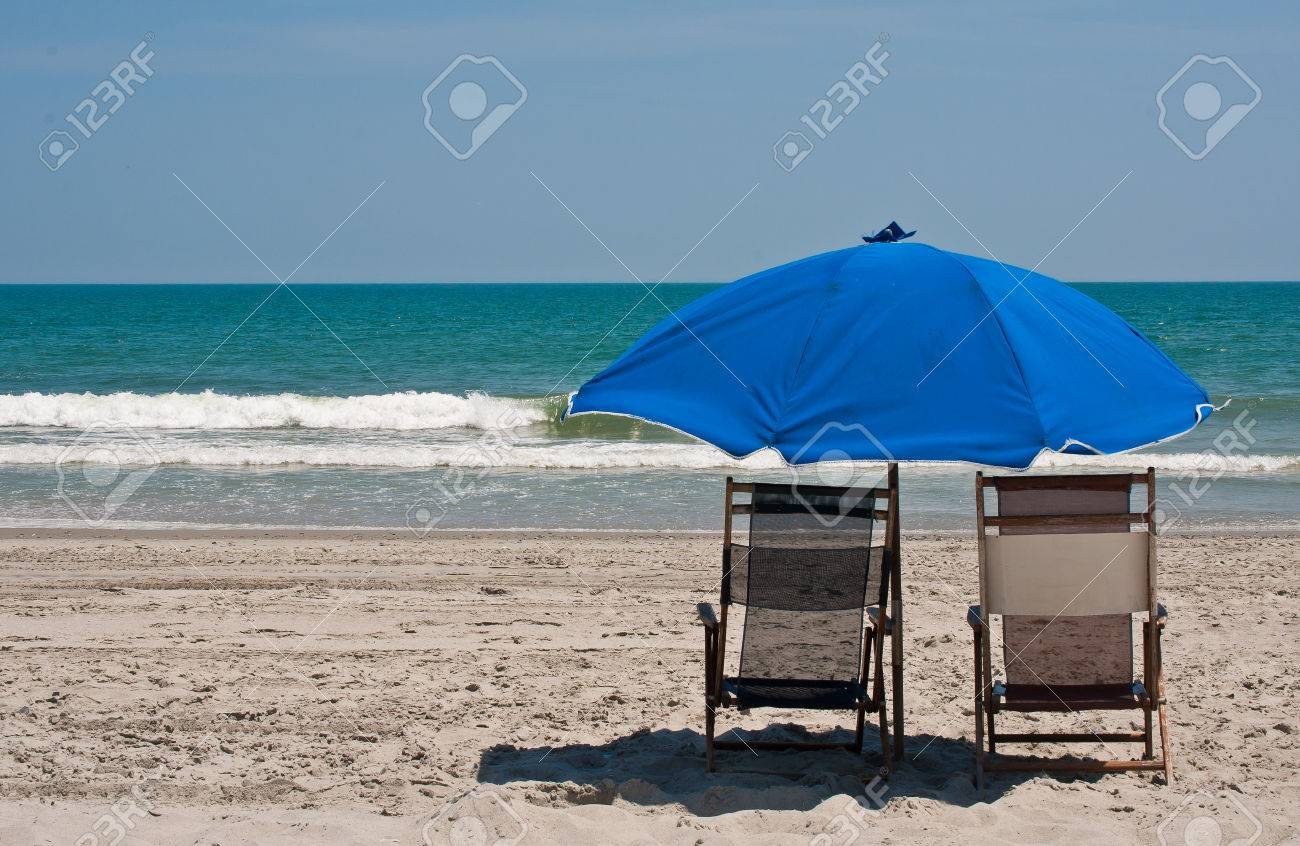 Beach chair and umbrella set - Stock Photo Two Beach Chairs With A Blue Umbrella Set In Beautiful White Sand With Blue Ocean Waters And Clear Sky In Background Copy Space Available