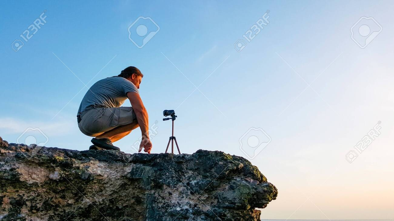 Travel photographer man sitting on the rock and taking nature video of beautiful sunset on the beach. Hiker tourist professional videographer on adventure vacation shooting by video camera on tripod. - 126283531