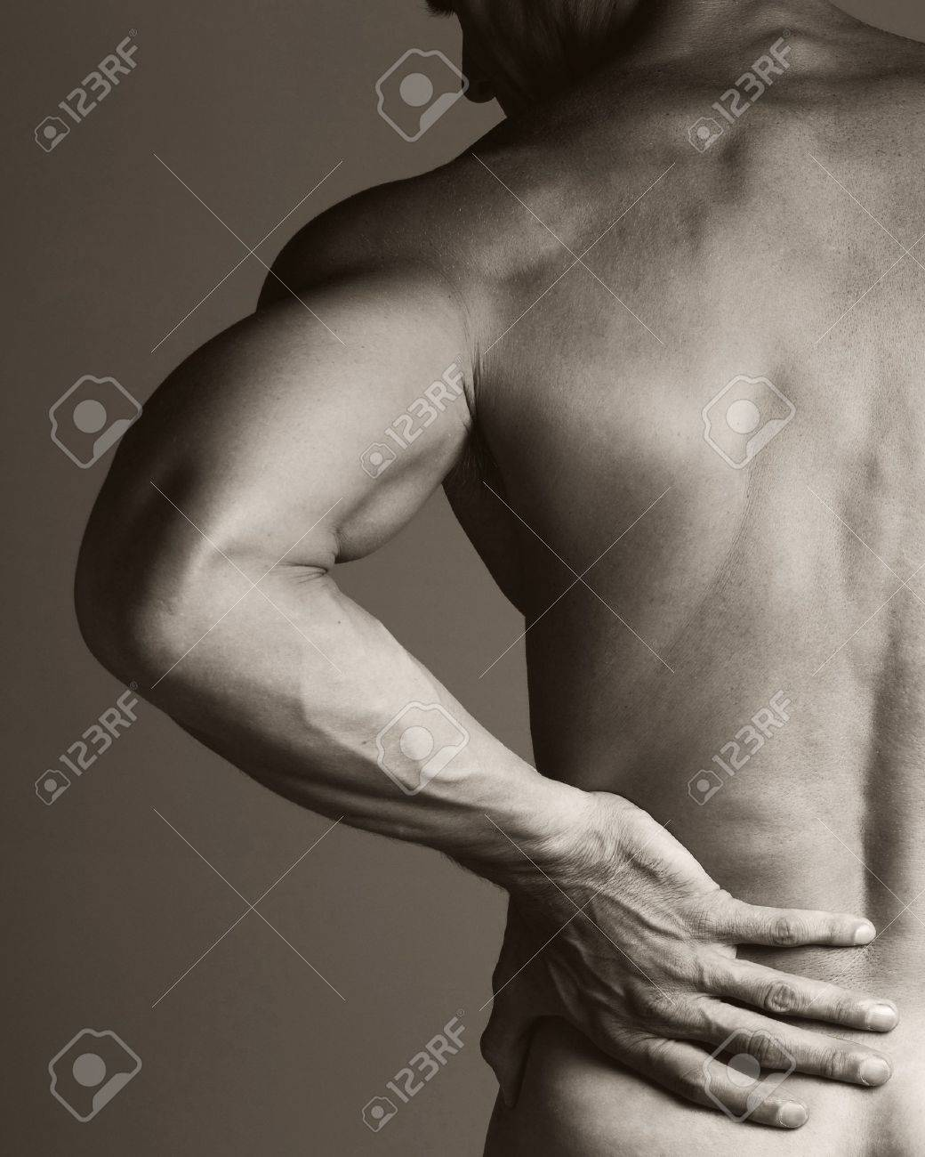 A black and white image of a muscular man holding his lower back as if experiencing a backache Stock Photo - 15335600