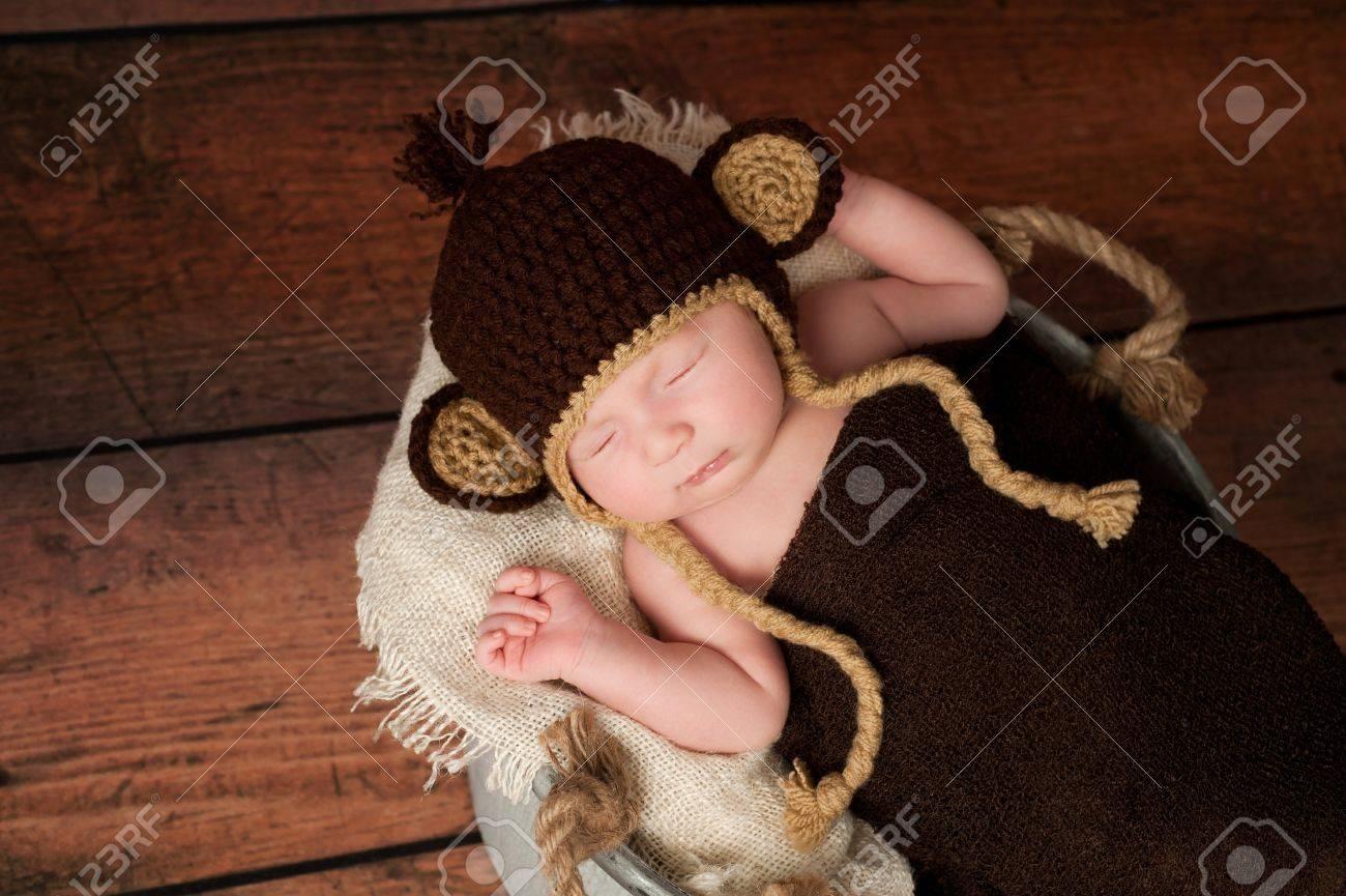 Foto de archivo - Un bebé recién nacido con un sombrero del mono de ganchillo  y durmiendo en un cubo galvanizado Filmada en el estudio con un fondo de ... 2c82c0234c3