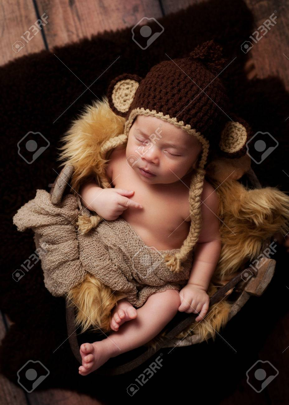 A newborn baby boy wearing a crocheted monkey hat and sleeping in an antique  wooden well 8b3abbf17adc
