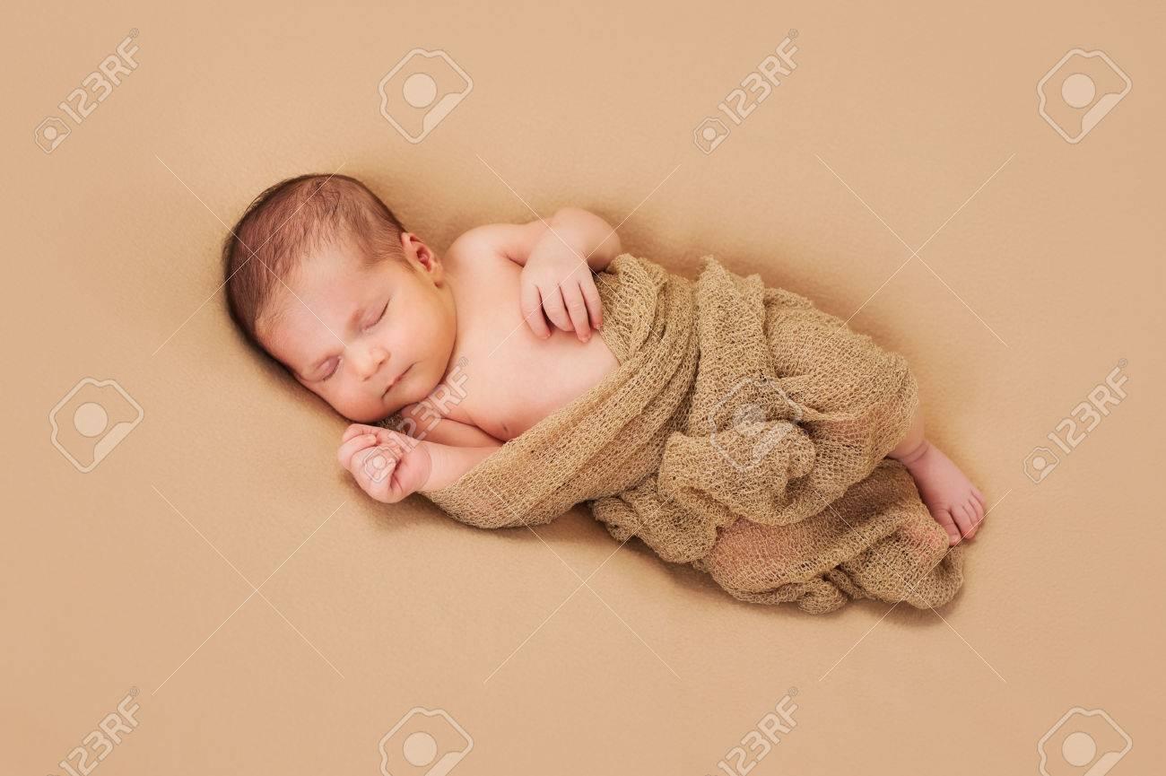 A 3 Week Old Newborn Baby Boy Wrapped In Gauzy Beige Fabric And