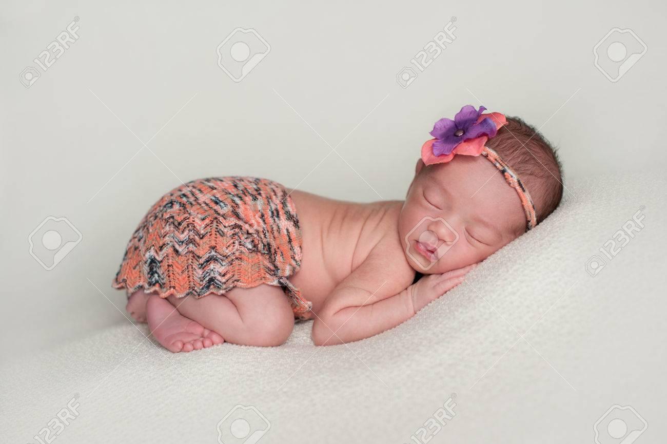 23a424a9d6 Archivio Fotografico - Un ritratto di una bella undici giorni di età bambina  indossare un mini gonna e la congruenza fascia arancione. Lei dorme sulla  sua ...