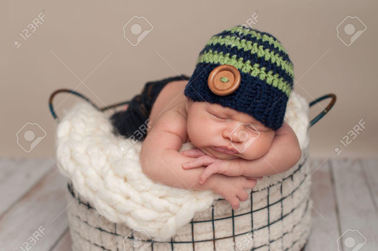 a89d9f948 Foto de archivo - Tres semanas de edad bebé recién nacido con pantalones  vaqueros y un ganchillo azul y verde gorro. Él está durmiendo boca abajo en  una ...