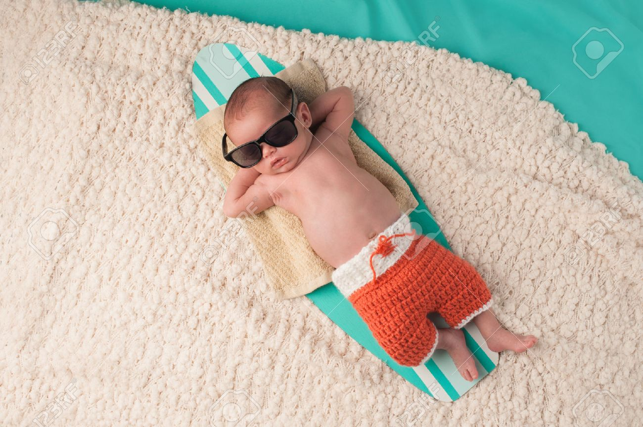 Newborn baby boy sleeping on a tiny surfboard. He is wearing black sunglasses and crocheted boardshorts. Stock Photo - 43716455