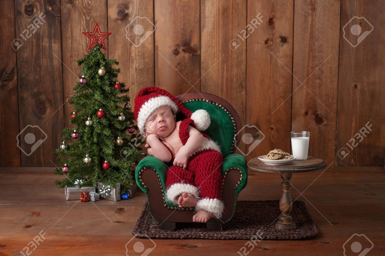 3101e38f8 Two week old, newborn, baby boy wearing a crocheted Santa suit. He is  sleeping on a tiny armchair. Shot in the studio with props, including a  Christmas tree ...