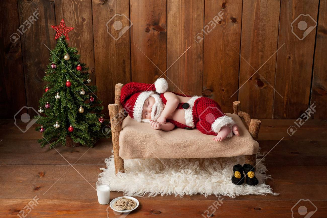 3a1b381a4 Two week old, newborn, baby boy wearing a crocheted Santa suit and sleeping  on a tiny, wooden bed. Shot in the studio with props, including a Christmas  tree ...