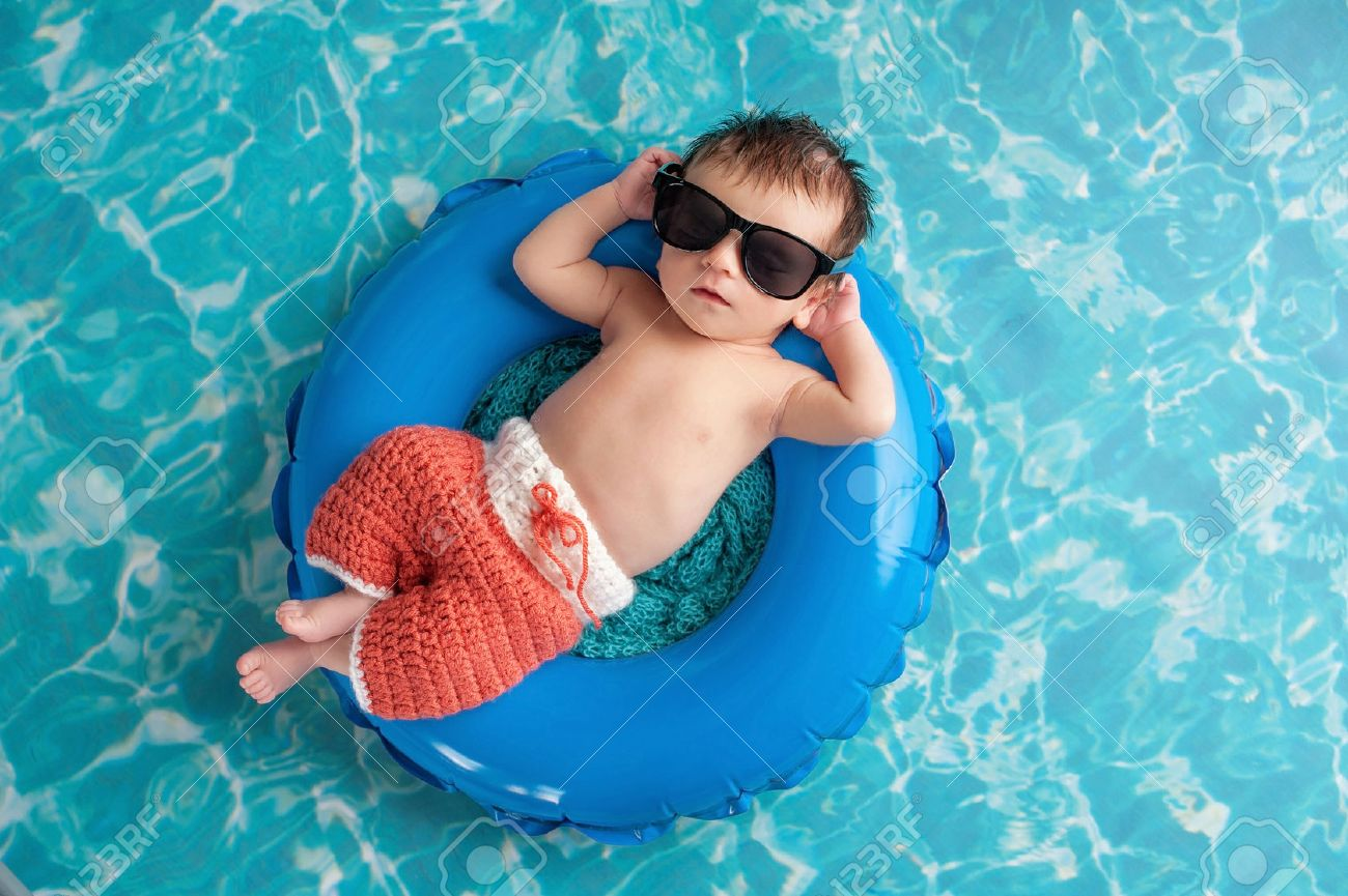 Three week old newborn baby boy sleeping on a tiny inflatable swim ring. He is wearing crocheted board shorts and black sunglasses. - 48645122