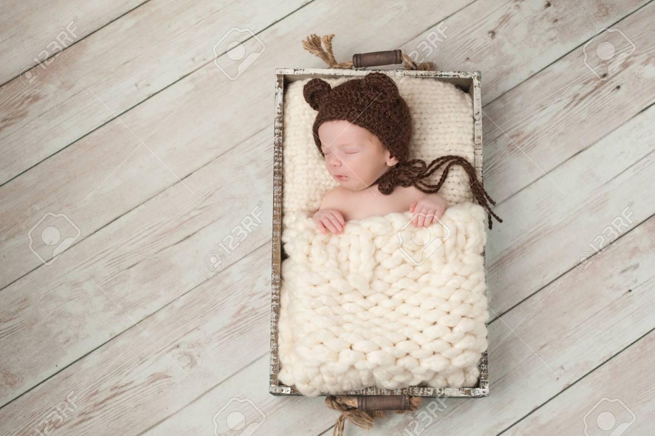 Dos semanas de edad bebé recién nacido que lleva un marrón, de punto, capo  oso. Él está durmiendo en una caja de madera rústica. Un disparo en ...