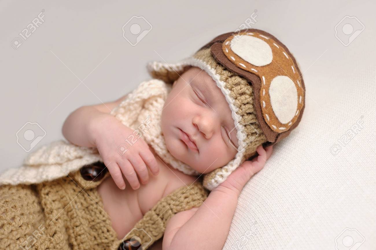 0c373a917 Sleeping two week old newborn baby boy wearing a crocheted aviator..