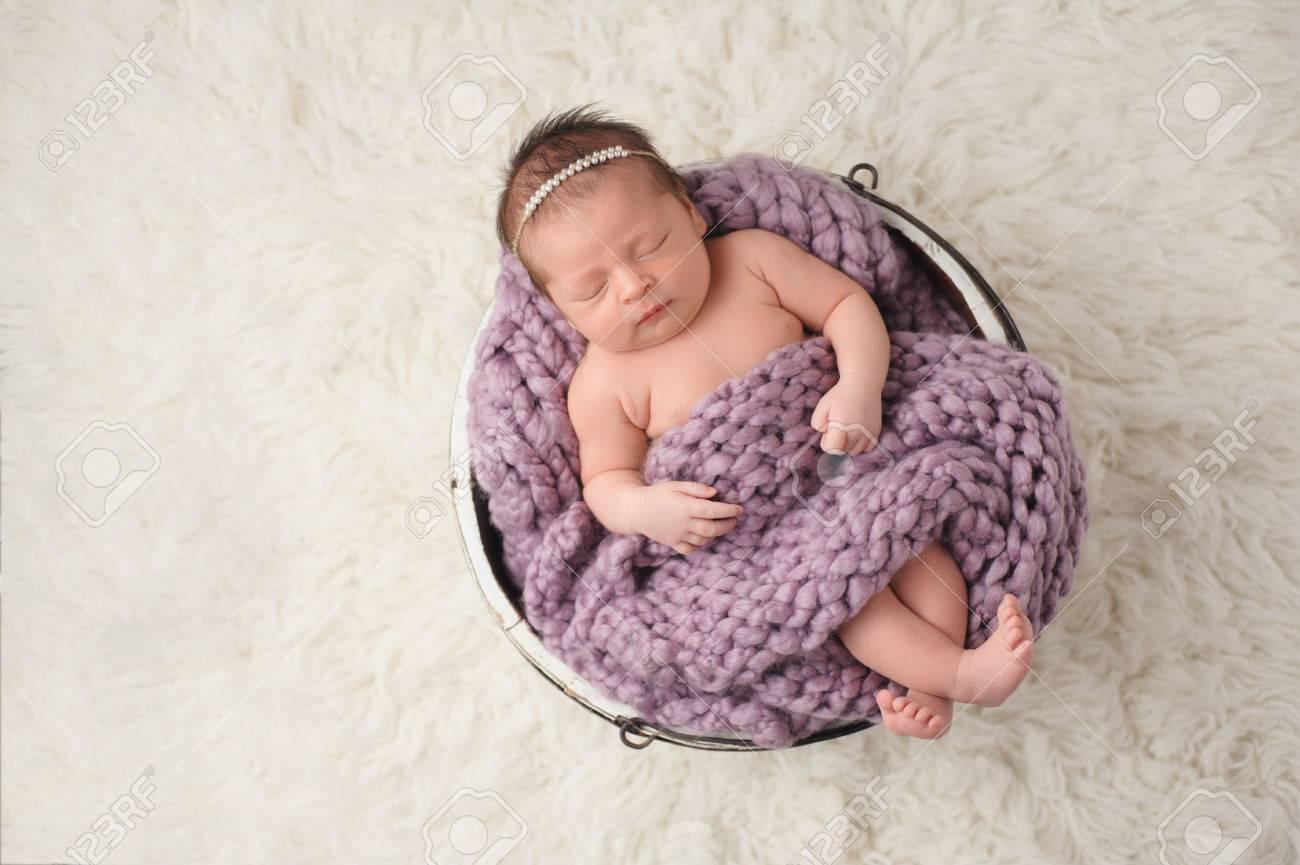 2c431dafaf Una bambina neonata di nove giorni che dorme in un piccolo secchio di legno.  È coperta da una coperta colorata lavanda e coperta.