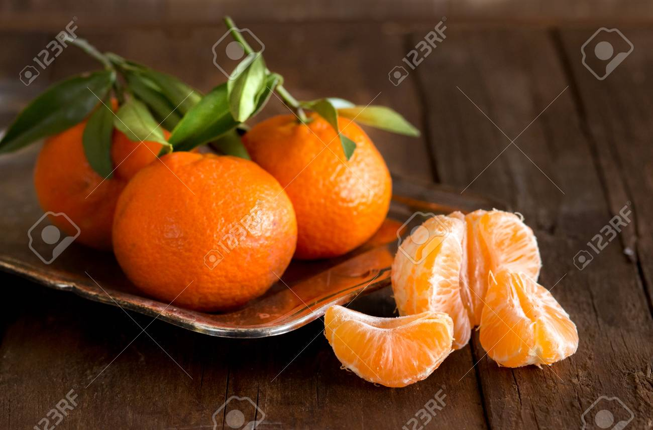 Fresh Tangerines with green leaves on a wooden background - 34562628