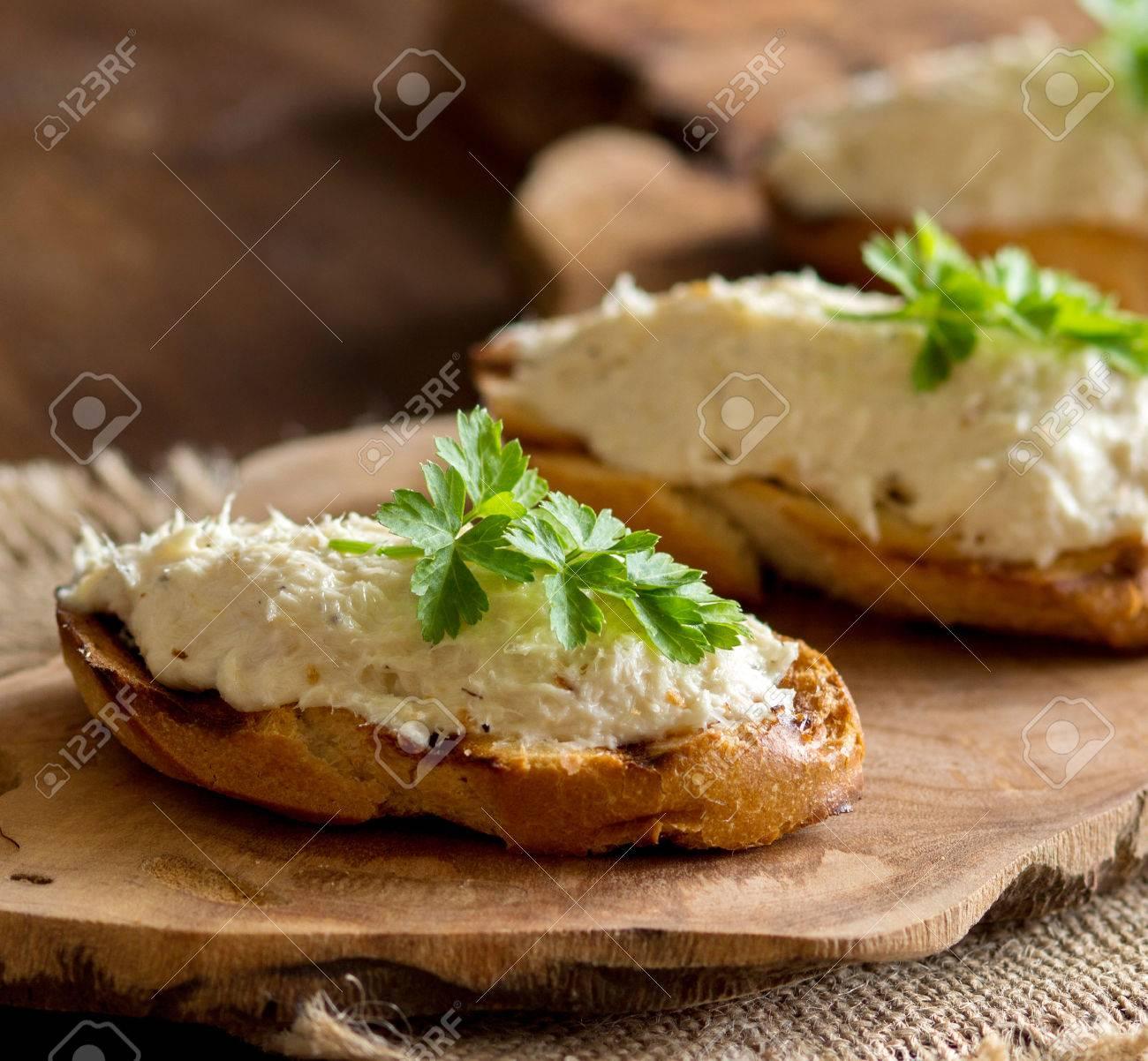 Pane tostato con mousse baccalà salato sul tagliere di legno Archivio Fotografico - 35193256