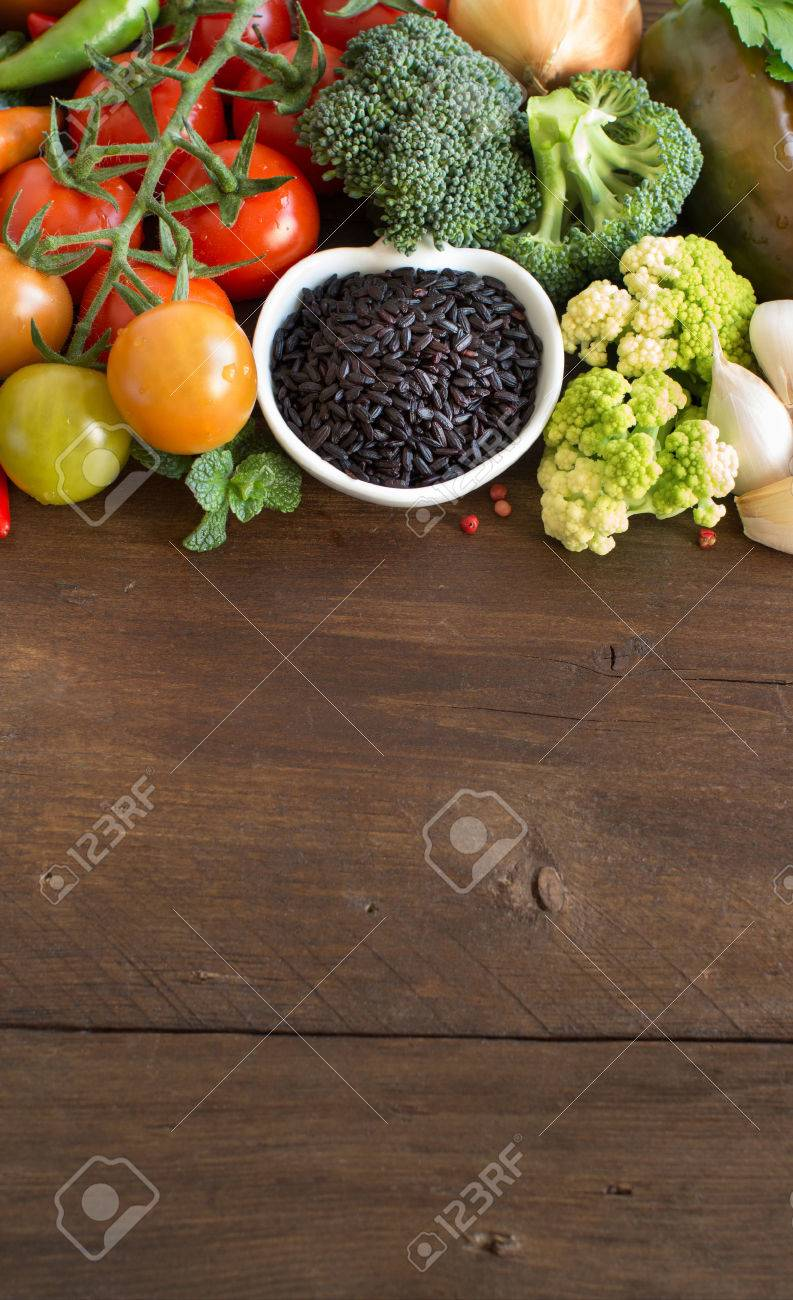 Uncooked black rice in a bowl with vegetables on wood Archivio Fotografico - 51801278