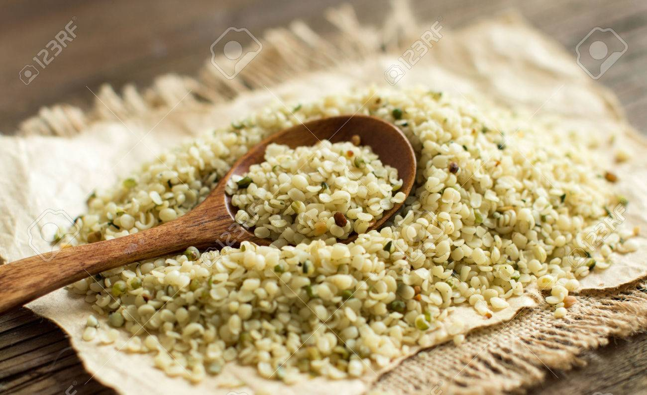 Pile of Uncooked Hemp seeds with a spoon close up Archivio Fotografico - 52232433